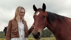 Young woman smiles, hugs brown horse outdoor  gimbal steadicam Stock Footage
