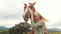 Blonde young woman smiles, strokes and hugs brown horse outdoor Stock Footage