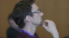Man stroking his chin and listening to a presentation at a conference - stock footage