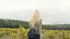 Back view of beautiful blond young girl walks outdoor in nature Stock Footage