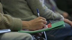 Person sat in the audience and writing notes at a conference - stock footage