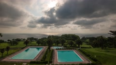 Panning time-lapse footage of the morning sky over swimming pools Stock Footage