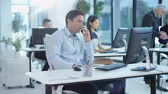 4KCall centre operators in city office working on computers talking to customers - stock footage