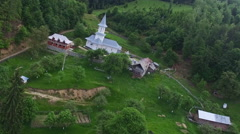 Christian church on top of green hill surrounded by forest, aerial flight Stock Footage