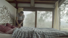 Young man makes a bed in the morning Stock Footage