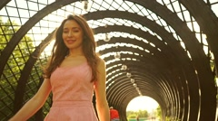 Beautiful brunette girl in pink dress walks though arched passage. Slow motion Stock Footage