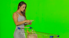 Woman shopping with trolley at supermarket and checking a paper list. Green Stock Footage