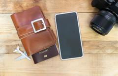Travel item photo camera, Passports,  smart, phone devices on a wooden floor. Stock Photos
