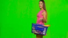 Woman with a basket enjoying the scent of pepper. Green screen - stock footage