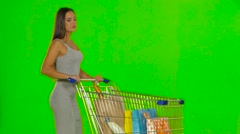 Woman with the trolley makes a turn and stops. Green screen Stock Footage