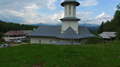 Christian church on top of green hill with mountain range, cam fly Stock Footage