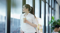 4K Businesswoman looking at view from window & discussing work with coworker Stock Footage