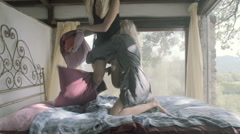 Two young women do a pillow fight on bed Stock Footage