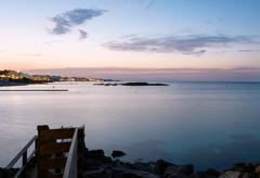 sea in protaras, cyprus island, with rocks and hotels at sunset. - stock photo