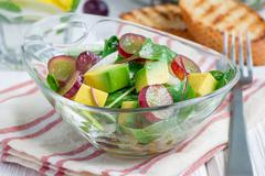 Vegetarian salad with avocado, grape, rucola, onion, in glass bowl Stock Photos