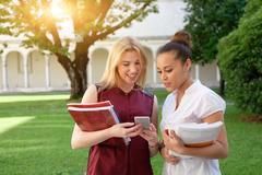 Two young females friends all together looking at mobile phone Stock Photos