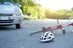 Broken bicycle on the asphalt after car crash incident Kuvituskuvat