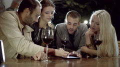 Group of friends uses tablet while drinks wine in rural farm house Stock Footage