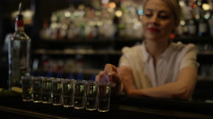 4K Portrait of smiling female bartender setting light to row of shot glasses Stock Footage