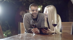 Couple in love smiles with wine uses tablet in rural farm house Stock Footage