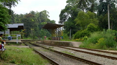 PEOPLE CROSS RAILWAY TRACKS PERADENIYA SRI LANKA Stock Footage