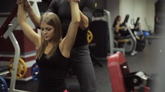 Woman performs a bench press dumbbells over your head, under guidance of a coach - stock footage