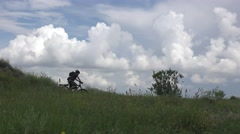 Male cyclist riding on bicycle edge of the cliff, river and white clouds Stock Footage