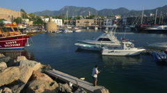 BOY FISHING IN HARBOUR KYRENIA NORTHERN CYPRUS Stock Footage