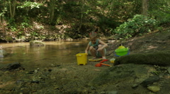 Little female child playing with colorful toys by the mountain river, dolly shot Stock Footage