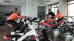 Couple engaged on a stationary bike in gym Stock Footage
