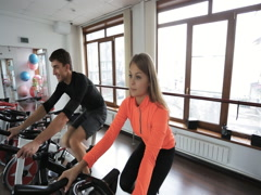 Couple on a stationary bike at gym with big windows Stock Footage