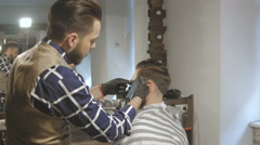 Men's hairstyling and haircutting with hair clipper in a barber shop or hair Stock Footage