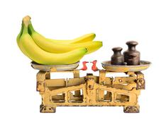 Bananas on the old fashioned scales with kettlebells. Isolated on white backg Stock Photos