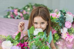 Portrait of a pretty little girl in a turquoise dress sniffs a flowers in a s - stock photo