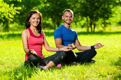Young man and woman doing yoga in the sunny summer park Stock Photos