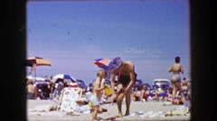 1955: Thin caucasian man taking toddler son to crowded summertime beach. Stock Footage