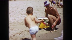 1955: Dad toddler boy playing beach sand bucket shovel toy ship. Stock Footage