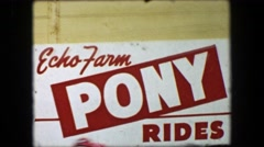 1956: Echo Farm kids pony ride boys ride horses around circle path track. Stock Footage
