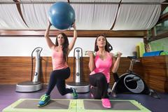 Two women exercise weights stability ball one leg lunge stepper - stock photo