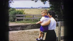 1956: Mother toddler son watching horse ranch riders in stable pens. Stock Footage