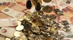 Coins fall on the notes and turn in slow motion Stock Footage