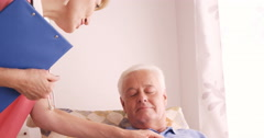 Female doctor consoling to a senior patient Stock Footage