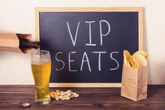 ?eer is poured into glass, chips, pistachio and handwriting text VIP seats wr Stock Photos