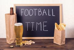 football fans setting of beer bottle in brown paper bag,  glass, chips, pista - stock photo