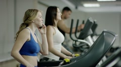 young smiling blond woman walking on treadmill - stock footage