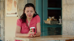 Sitting at a coffee shop, a beautiful young woman drinking coffe or tea. - stock footage