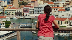 Young woman is admiring of top view to Greek colorful town Agios Nikolaos. Stock Footage
