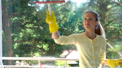 Young attractive woman cleaning a window and smiling at camera. Dolly shot. Stock Footage