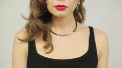 Beautiful woman with red lipstick puts a finger to her lips - stock footage