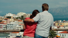 The couple of lovers admiring of top view Agios Nikolaos town. Stock Footage